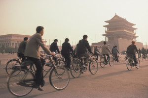 Commuters cycle past Tiananmen Square in Beijing